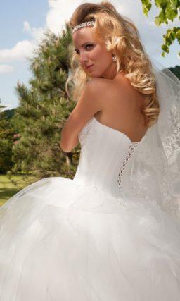 Впечатляющее свадебное платье с пышной юбкой, покрытой оборками, и открытым корсетом.