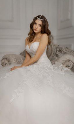 Свадебное платье с открытым лифом, дополненным кружевными рукавами, и пышной юбкой.