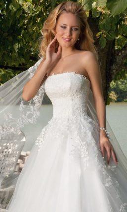 Открытое свадебное платье силуэта «принцесса» с фактурной отделкой из аппликаций на корсете.