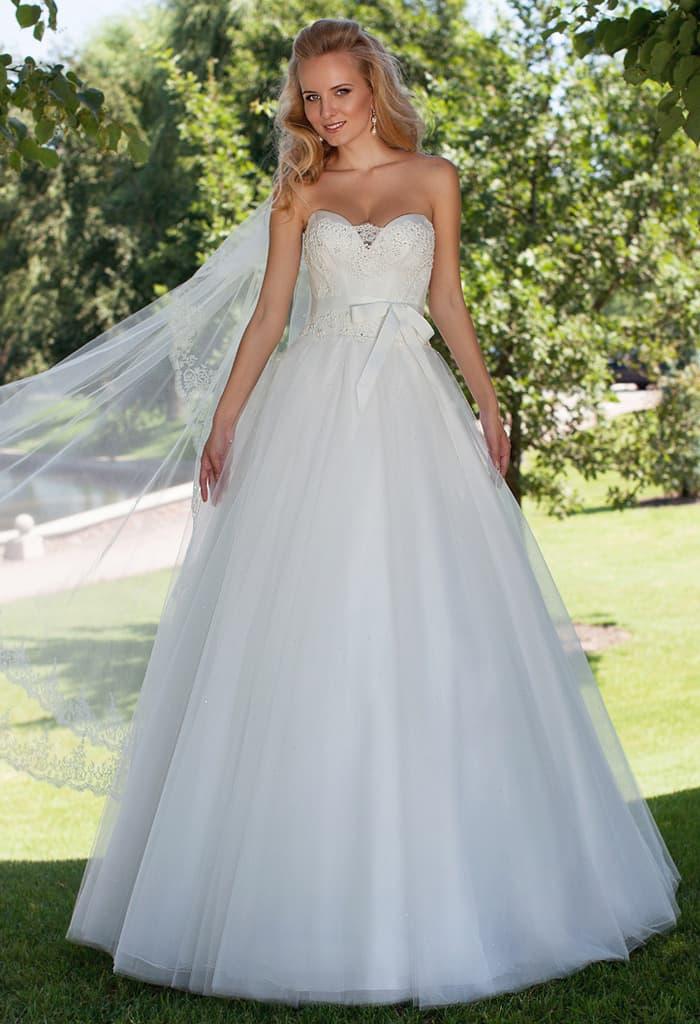 Кокетливое свадебное платье А-силуэта с поясом с бантом и кружевной отделкой лифа.