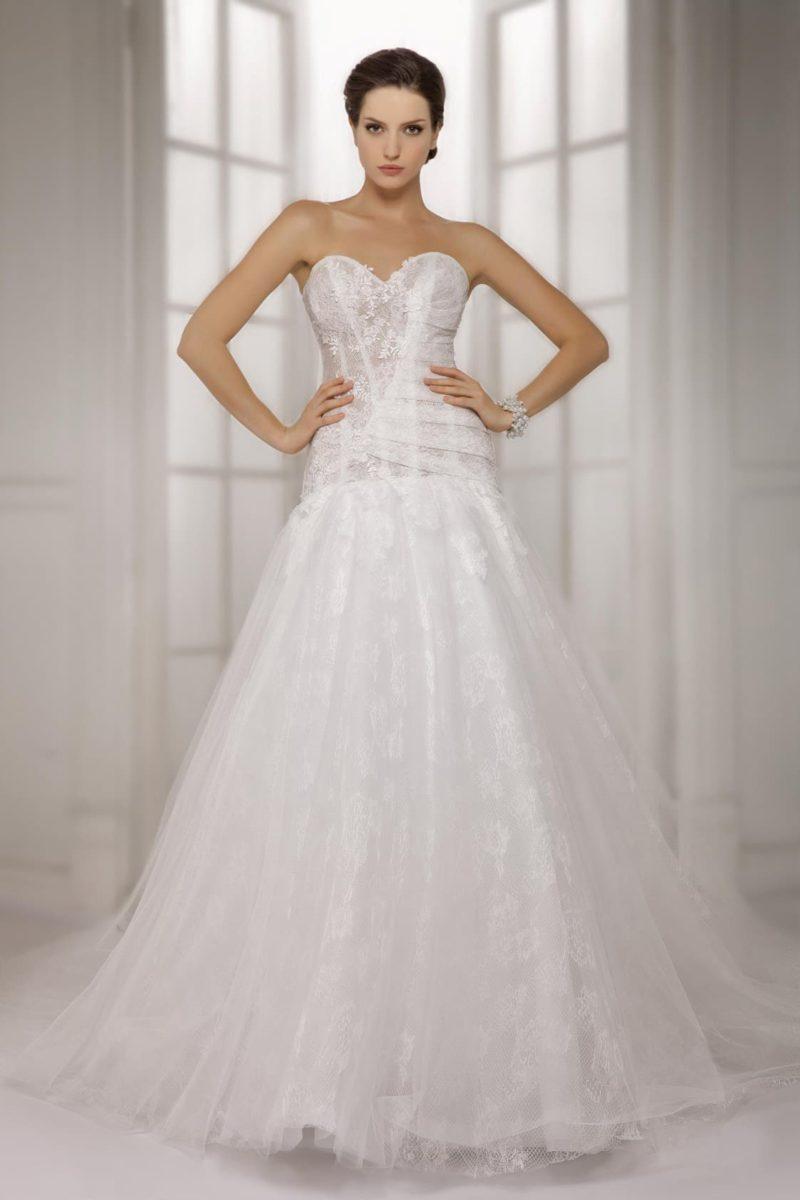 Стильное свадебное платье с открытым лифом в форме сердца и многослойной юбкой.