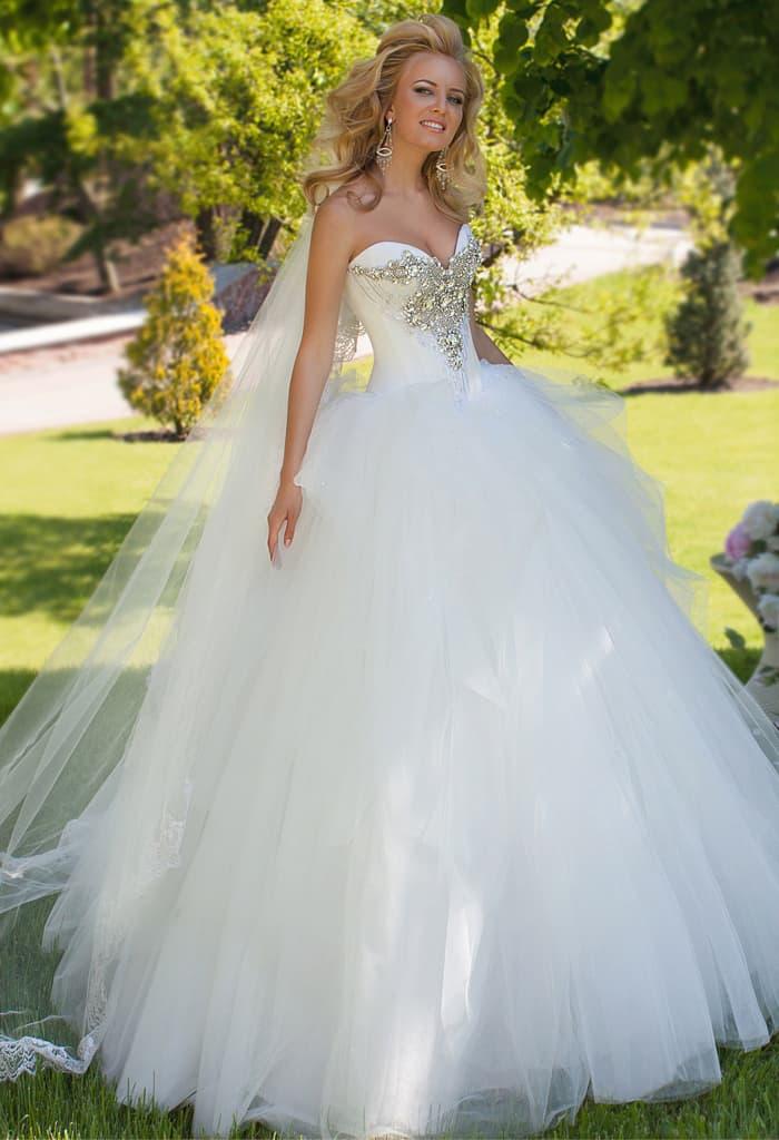 Великолепное свадебное платье с пышной юбкой, спускающейся волнами, и стразами на лифе.