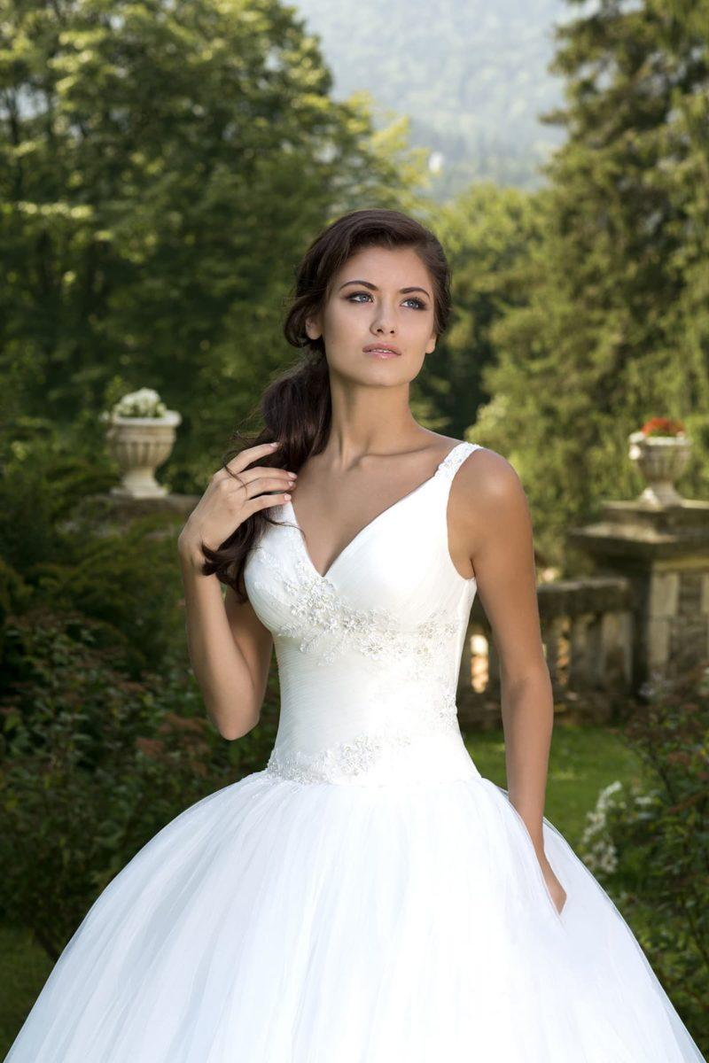 Безупречное свадебное платье с глубоким V-образным декольте и юбкой пышного силуэта.