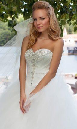 Открытое свадебное платье с лифом классического кроя и пышной многослойной юбкой.