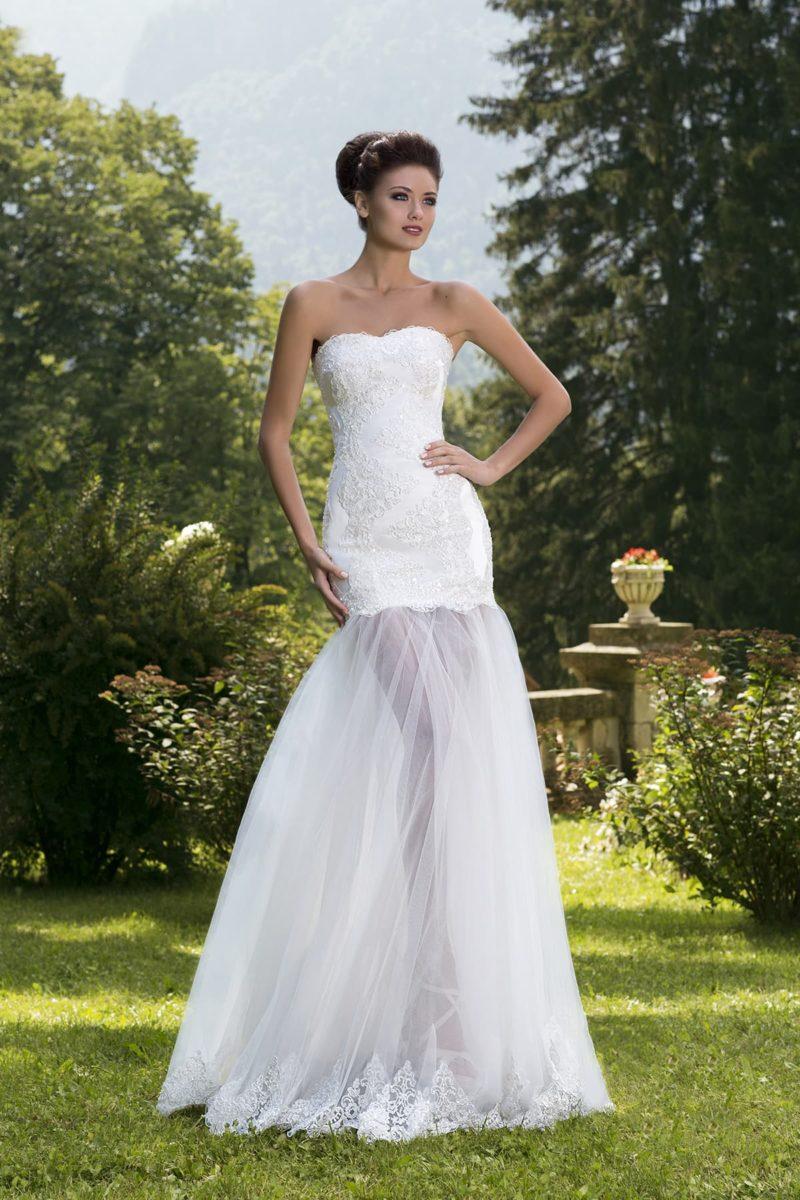 Открытое свадебное платье с корсетом, декорированным глянцевыми аппликациями, и прозрачной юбкой.