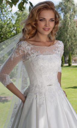 Свадебное платье с юбкой А-силуэта из глянцевой ткани и изящными ажурными рукавами.