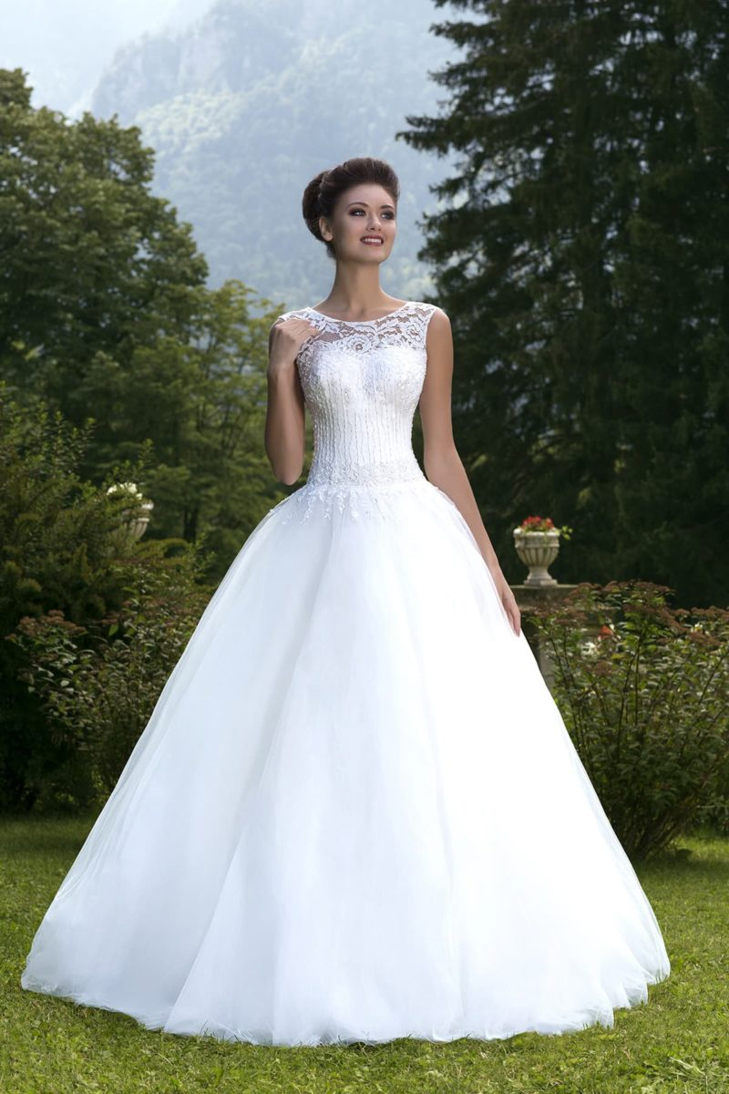 Пышное свадебное платье с округлым декольте и широкими ажурными бретелями.