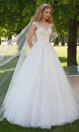 Закрытое свадебное платье с ажурным верхом и многослойной юбкой из полупрозрачной ткани.