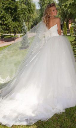 Свадебное платье пышного силуэта с глубоким декольте на атласном лифе с вышивкой.