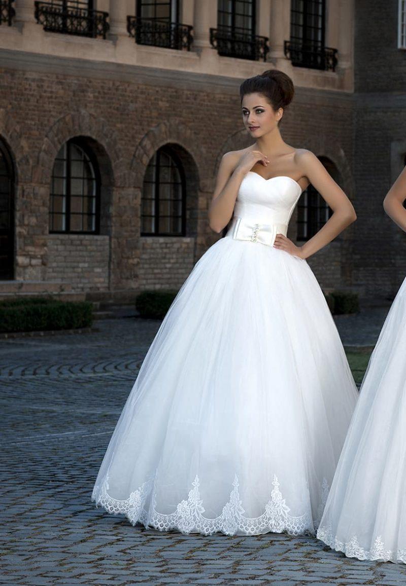 Изысканное свадебное платье с торжественным пышным силуэтом и атласным поясом с бантом.