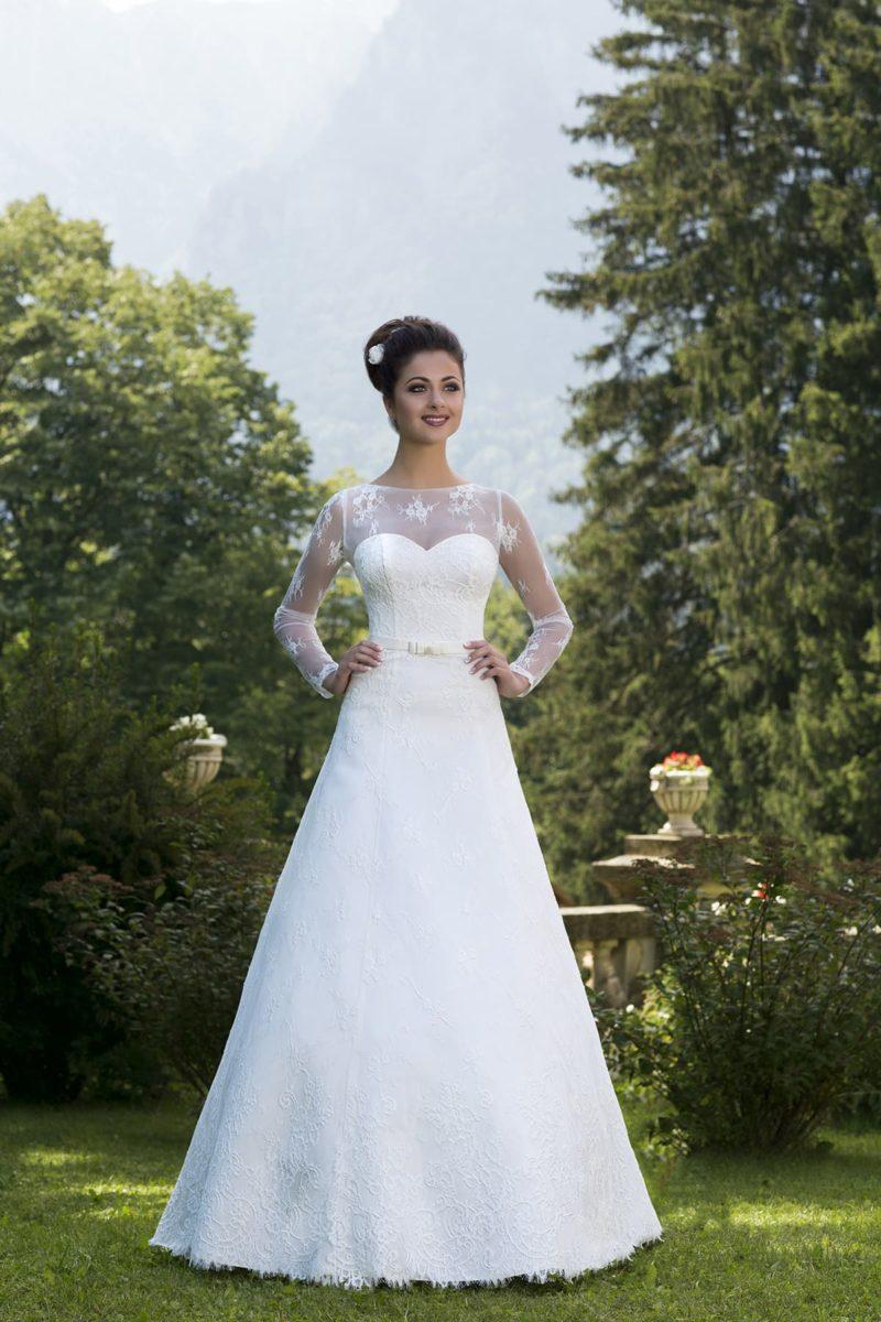 Скромное свадебное платье А-силуэта с ажурными рукавами длиной до запястий.