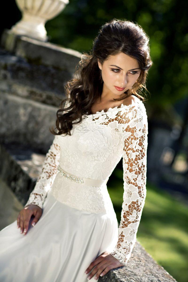 Свадебное платье с прямой юбкой из атласной ткани и длинными ажурными рукавами.