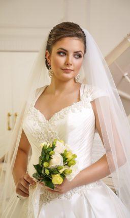 Пышное свадебное платье с роскошной атласной юбкой и широкими бретелями.