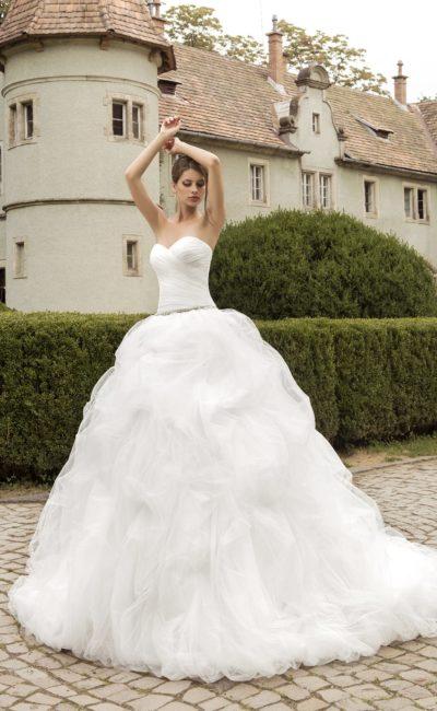 Пышное свадебное платье с нежными драпировками на корсете и объемным декором подола.