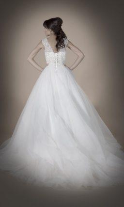 Пышное свадебное платье с юбкой из полупрозрачной ткани и ажурными бретелями.