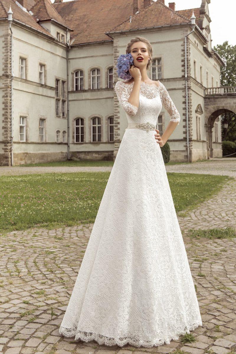 Атласное свадебное платье силуэта «принцесса» с ажурными рукавами и широким поясом.