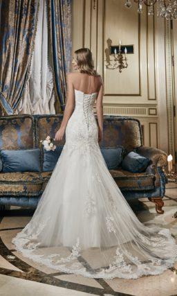 Открытое свадебное платье с пышным силуэтом «рыбка» и лифом, украшенным горизонтальными драпировками.