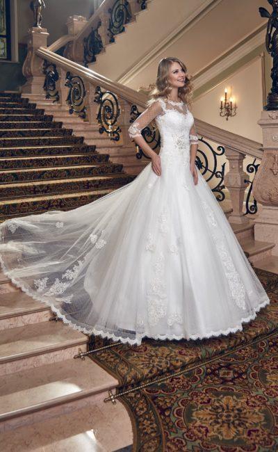 Пышное свадебное платье с кружевным декором верха и длинным полупрозрачным шлейфом.