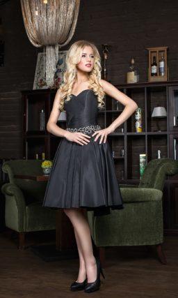 Коктейльное платье из плотной глянцевой ткани, дополненное сверкающим поясом.
