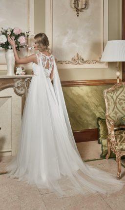 Свадебное платье в ампирном стиле с фигурными бретелями и длинной прозрачной накидкой сзади.
