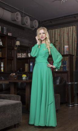 Закрытое вечернее платье с широким поясом и длинными рукавами с манжетами.