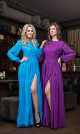 Закрытое вечернее платье с широкими рукавами и высоким разрезом на юбке.