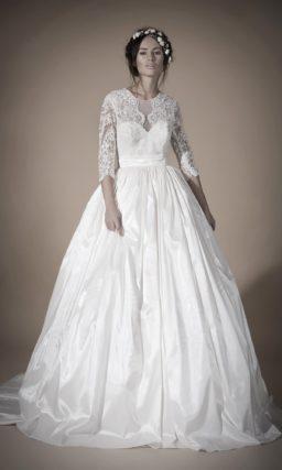 Закрытое свадебное платье с силуэтом «принцесса», атласной юбкой и кружевными рукавами.