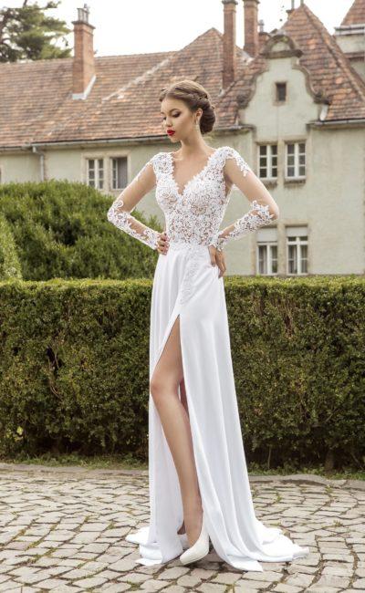 Прямое свадебное платье с разрезом на юбке и длинными кружевными рукавами.