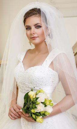 Пышное свадебное платье для полной невесты с соблазнительным лифом и юбкой, покрытой полупрозрачными оборками.