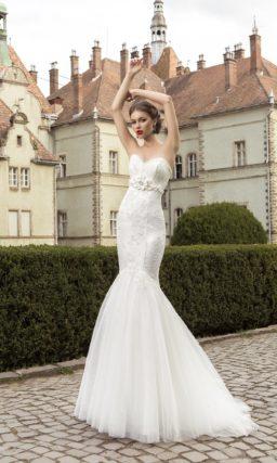 Свадебное платье силуэта «русалка» с кружевным декором и поясом, украшенным объемным бутоном.