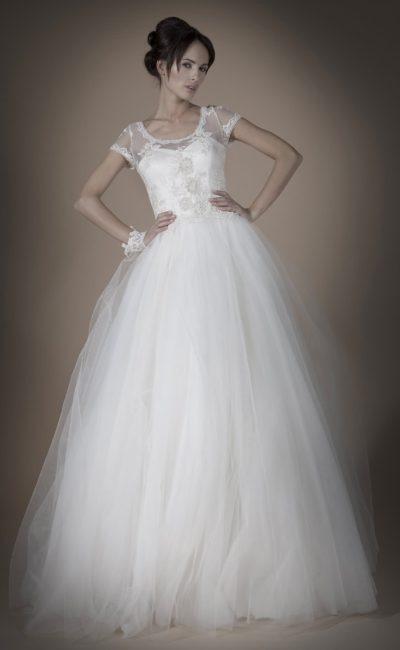 Пышное свадебное платье с роскошной многослойной юбкой и короткими облегающими рукавами.
