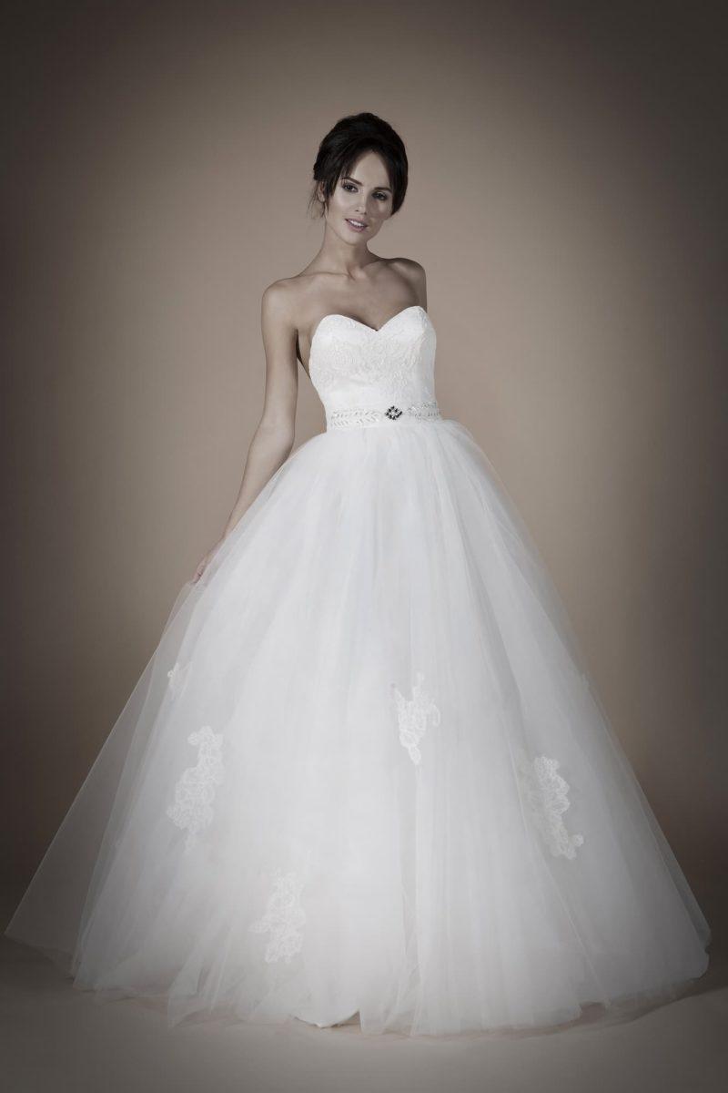 Открытое свадебное платье с пышной юбкой, украшенной кружевом, и широким поясом на талии.