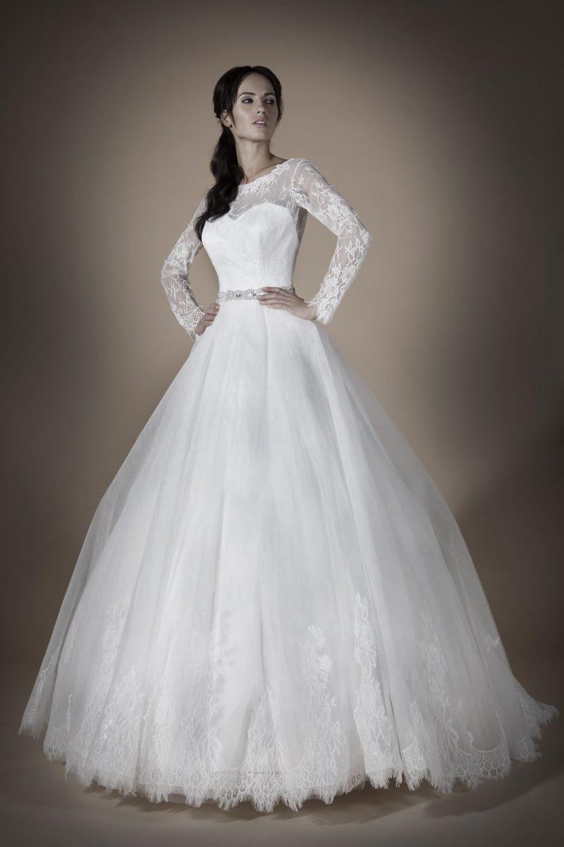 Пышное свадебное платье с кружевным декором юбки и длинными ажурными рукавами.