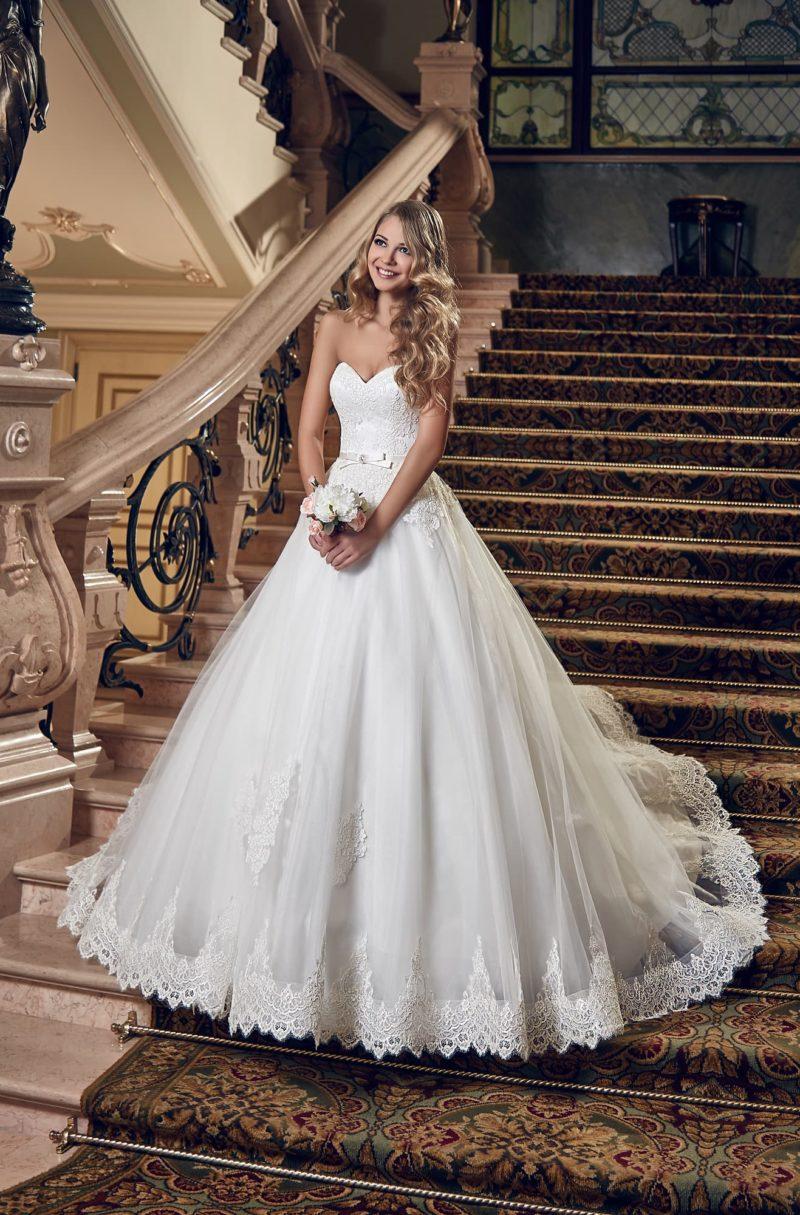 Открытое свадебное платье с декором из кружевных аппликаций и узким поясом на талии.