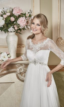Прямое свадебное платье с вертикальными складками на юбке и ажурными рукавами.