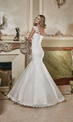 Кружевное свадебное платье с рукавами длиной три четверти и пышной баской над объемной юбкой.