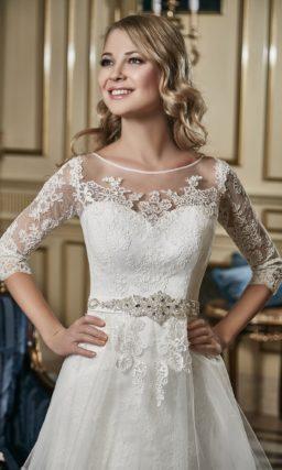 Кружевное свадебное платье с полупрозрачной верхней юбкой А-силуэта и длинным рукавом.