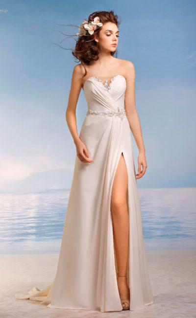 Прямое свадебное платье с необычной формы лифом с глубоким вырезом и разрезом сбоку на юбке.