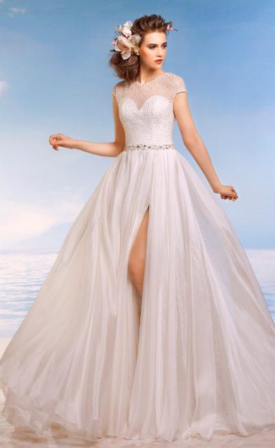 Прямое свадебное платье с короткими рукавами из ажурной ткани и разрезом на юбке.