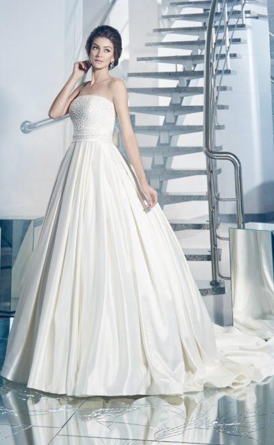 Атласное свадебное платье с пышной юбкой, украшенной вертикальными складками и шлейфом.