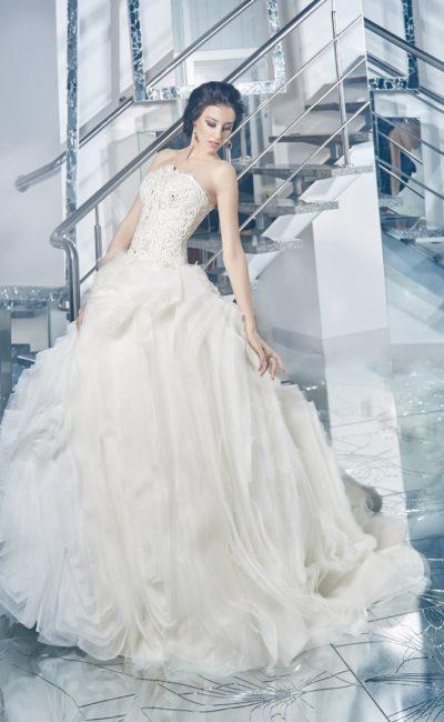 Открытое свадебное платье с расшитым корсетом и многослойной юбкой, покрытой оборками.