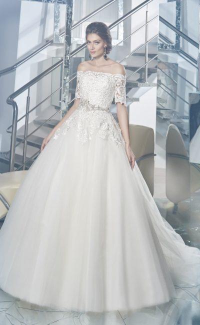 Пышное свадебное платье с глянцевым кружевом, покрывающим верх с портретным вырезом.