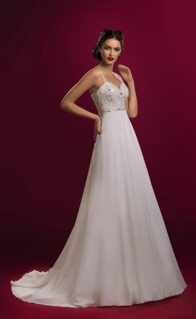 Свадебное платье прямого силуэта с лифом, украшенным серебристой вышивкой и дополненным бретелями.