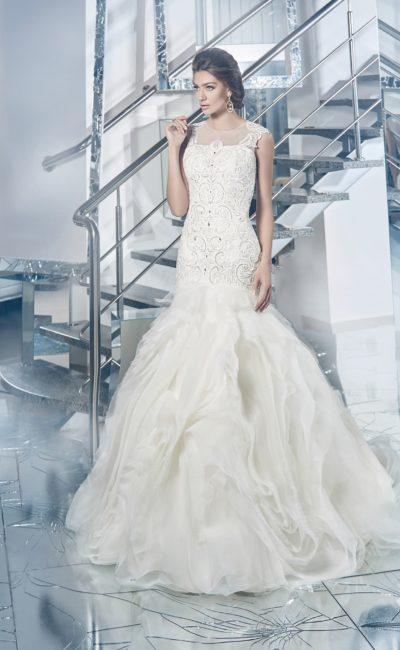Шикарное свадебное платье силуэта «рыбка» с полупрозрачным декором верха и пышным низом юбки.