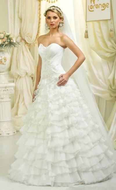 Роскошное свадебное платье силуэта «принцесса» с пышными оборками на юбке.