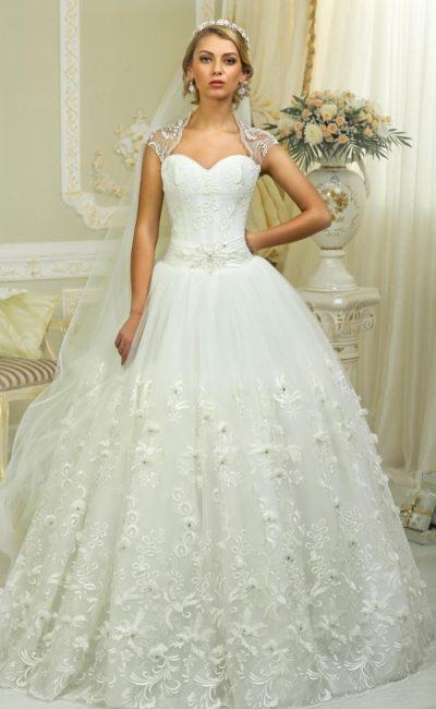 Пышное свадебное платье с вышивкой по многослойному подолу и кружевными бретелями.