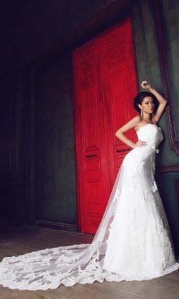 Прямое свадебное платье с открытым корсетом и полупрозрачной отделкой юбки со шлейфом.
