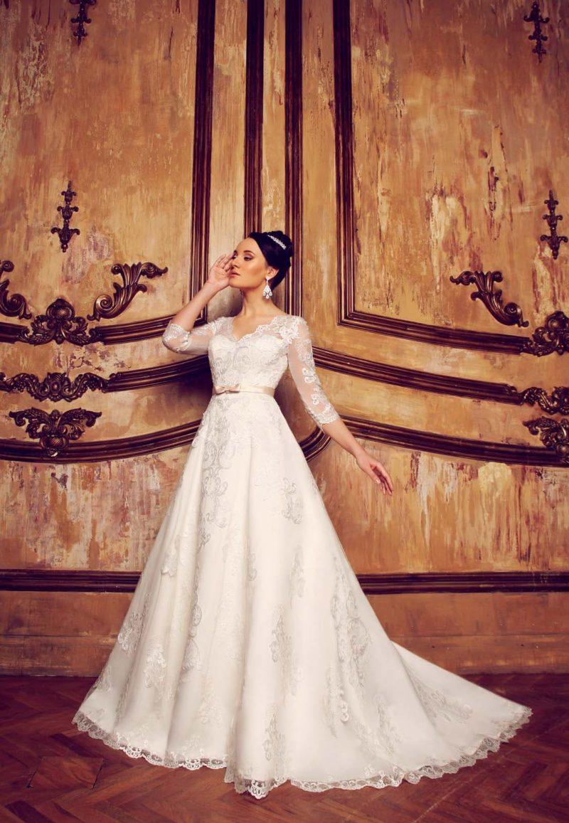 Закрытое свадебное платье силуэта «принцесса» с V-образным лифом и ажурными рукавами.
