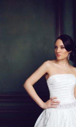 Пышное свадебное платье из фактурной глянцевой ткани с открытым лифом прямого кроя.