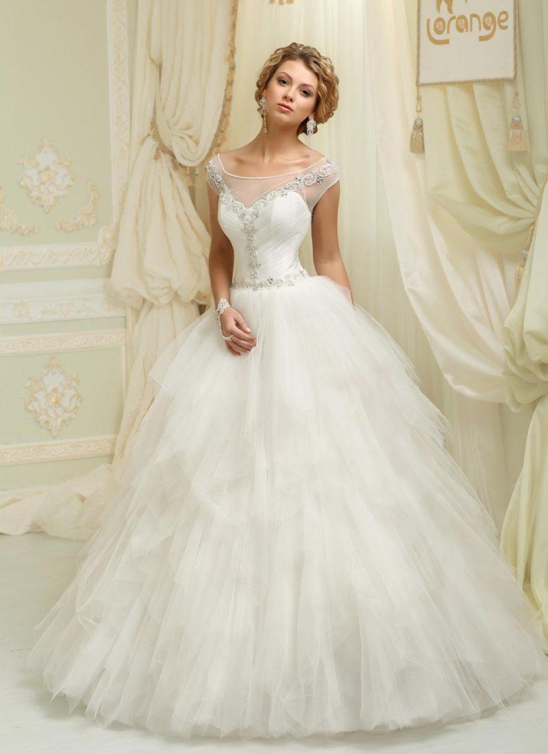 Пышное свадебное платье с полупрозрачными оборками на юбке и элегантным вырезом.
